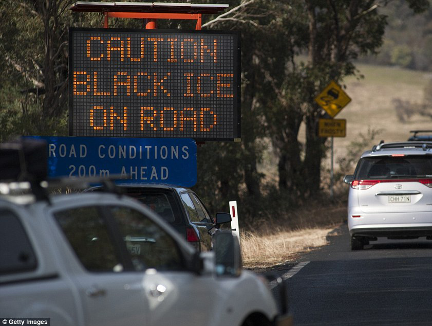 Cars driving on road next to a sign that reads: Caution black ice on road