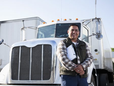 Truck driver (40s) standing in front of semi-truck with clipboard.